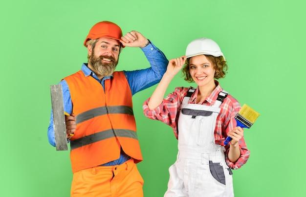Farbe wählen. diy-reparatur. bauarbeiter. renovierung des hauses. fröhliches paar, das haus renoviert. familiennest. wände streichen. frauenbauer-schutzhelm. mann ingenieur oder architekt. innenrenovierung.