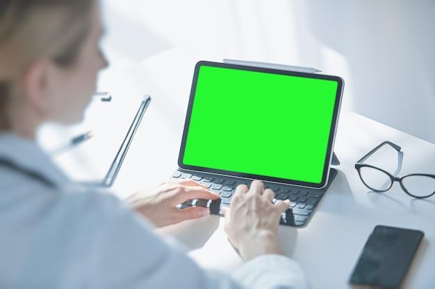 Farben – ein button auf dem tablet-bildschirm, ein blick über die schulter einer ärztin