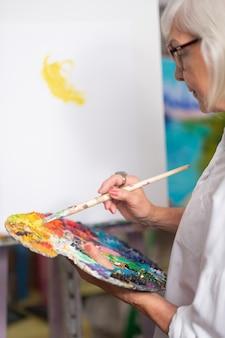Farben und farbe. gealterte frau, die weiße bluse hält, die farbpalette hält und mit gouache malt