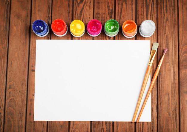 Farben und pinsel auf einem weißen leeren blatt papier auf holzuntergrund