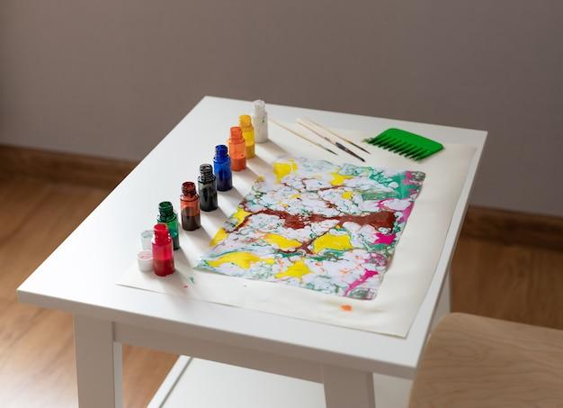 Farben und werkzeuge zum malen in ebru-technik auf tisch