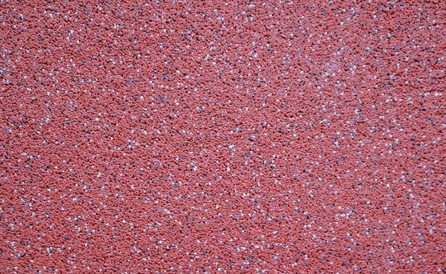 Farbenfroher dekorativer mosaikputz in burgund oder rot. wandbeschaffenheit, hintergrund. körnige, strukturierte, raue, ungleichmäßige strukturbeschichtung. moderne außenverkleidung.