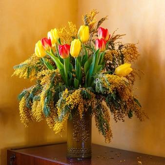 Farbenfroher glückwunsch-frühlingsstrauß aus tulpen und mimose in einer tonvase. kleiner fokus ausgewählt.