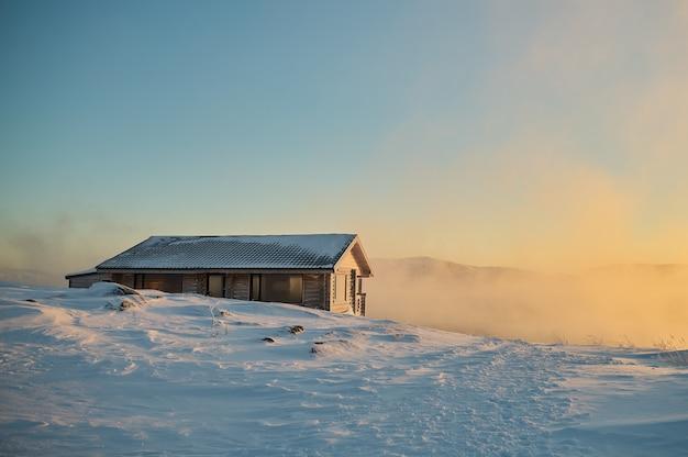Farbenfroher himmel bei sonnenuntergang oder sonnenaufgang in der wintersaison schneebedecktes feld und nebel mit einem himmel aus warmen farbtönen bei nebel im morgengrauen