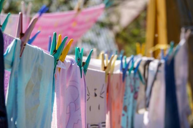 Farbenkleidung, die an der linie im garten hängt