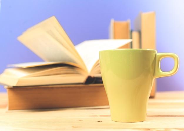 Farbentasse tee mit büchern auf tabelle
