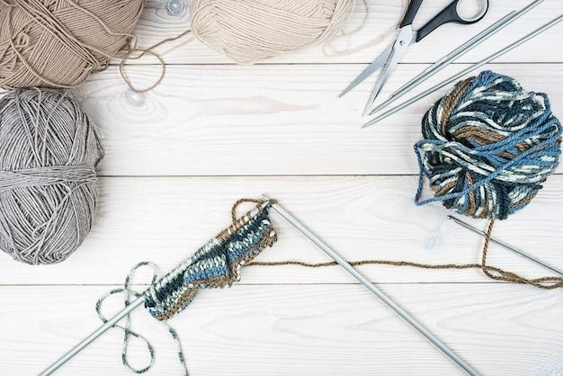 Farbfaden zum stricken, gestrickter schal, stricknadeln auf weißem holzhintergrund.