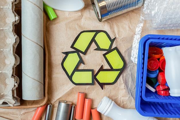 Farbige abfälle aus kunststoff, metalldosen, pappe, batterien und akkus mit recyclingschild auf papier