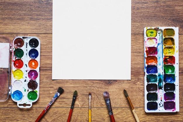 Farbige aquarellfarben und pinsel zum malen liegen auf dem hölzernen hintergrund