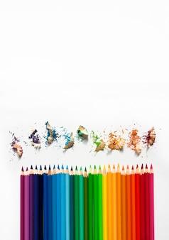 Farbige aquarellstifte auf weißem hintergrund. bleistifte spitzen. vertikales bild