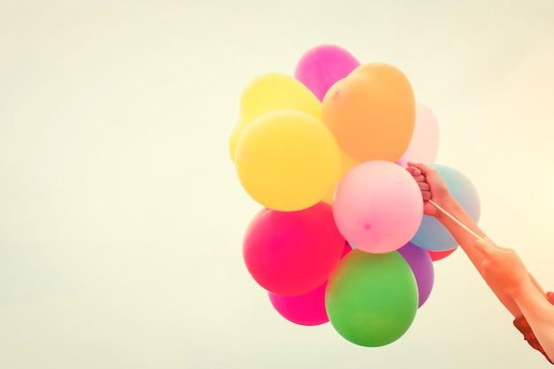Farbige ballons von armen gehalten