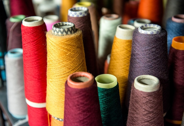 Farbige baumwollspulen auf pappkegeln