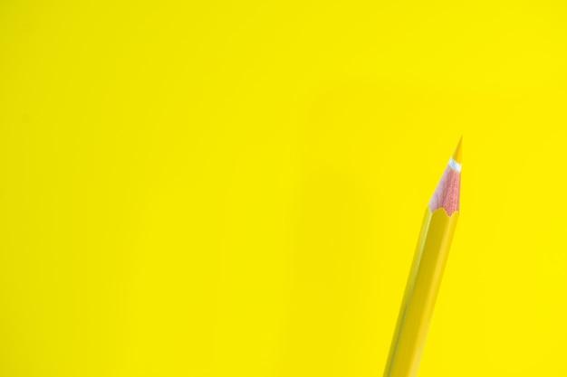Farbige bleistifte auf einem gelben hintergrund mit platz für text.