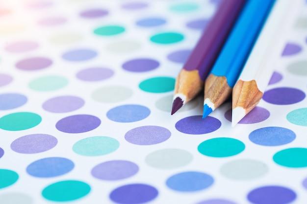 Farbige bleistifte auf einem pastellhintergrund zu einem punkt mit platz für text.