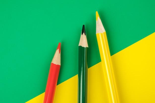 Farbige bleistifte auf farbpapierhintergrund