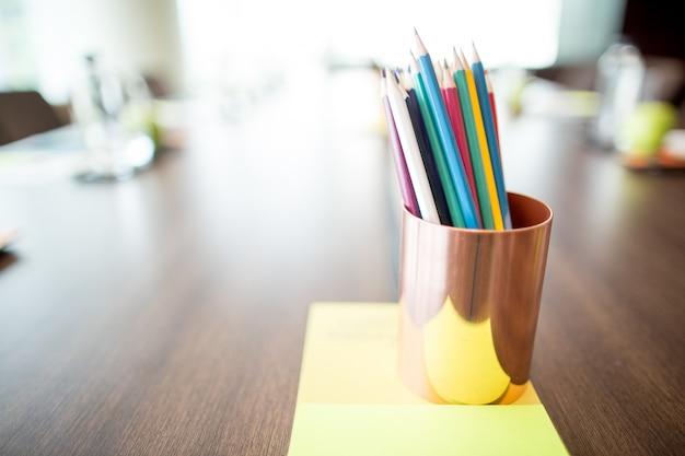Farbige bleistifte im cup auf konferenztisch