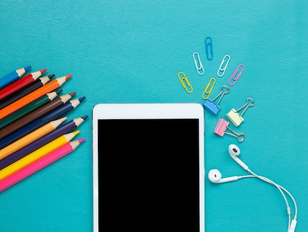 Farbige bleistifte und digitale tablette auf blau