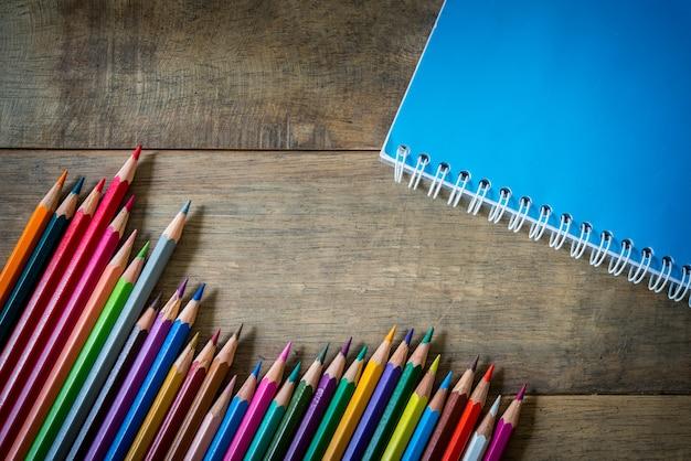 Farbige bleistifte und notizbuch auf holz