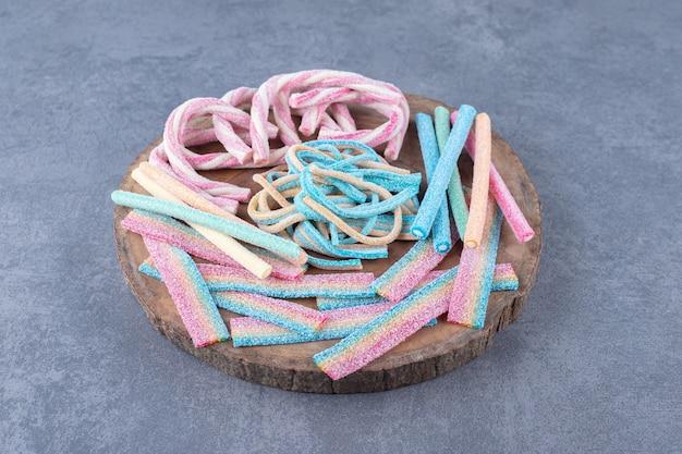 Farbige bonbons in form eines gedrehten seils auf einem brett, auf dem marmor.