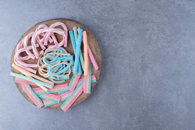 Farbige bonbons in form eines gedrehten seils auf einem brett