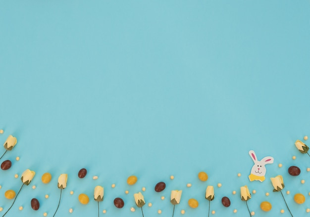 Farbige braune und gelbe schokoladen-ostereier-frühlingsblumen und hölzerner osterhase