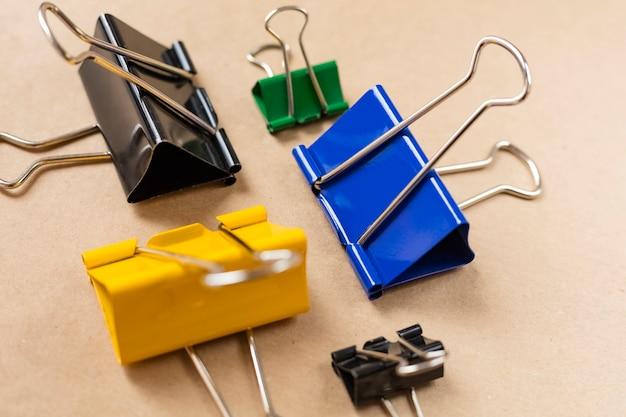 Farbige büroklammern auf einem braunen tisch. nahaufnahme. hintergrund, bastelpapier