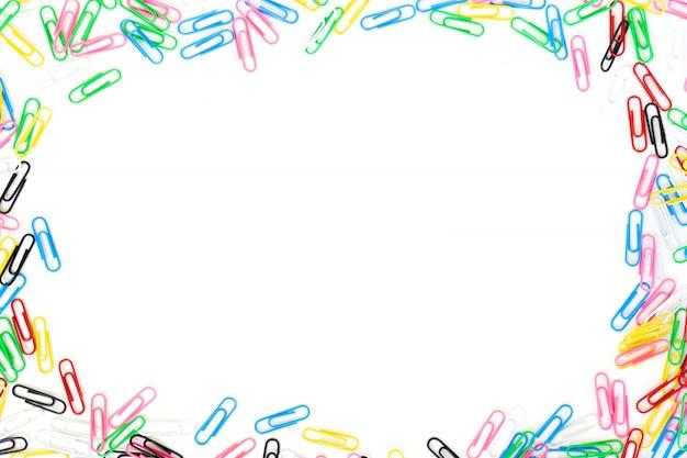 Farbige büroklammern verbreiteten auf rand mit dem mittelexemplar, das auf weiß getrennt wurde