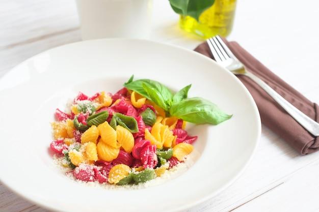 Farbige conchiglie-nudeln mit parmesan und basilikum