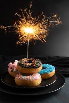 Farbige donuts mit wunderkerze, für geburtstagsfeier und feiern