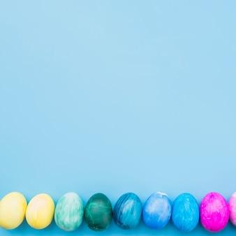 Farbige eier auf blauem hintergrund