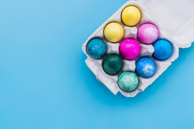 Farbige eier im kartongestell auf blauem hintergrund