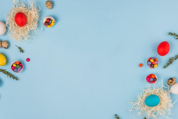 Farbige eier in nestern mit pflanzenzweigen und süßigkeiten
