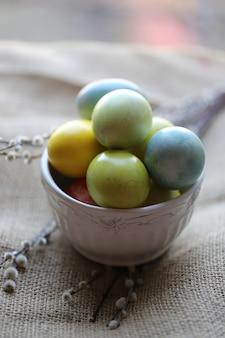 Farbige eier in selektiver weichzeichnung keramischen schüssel ostern-frühlinges