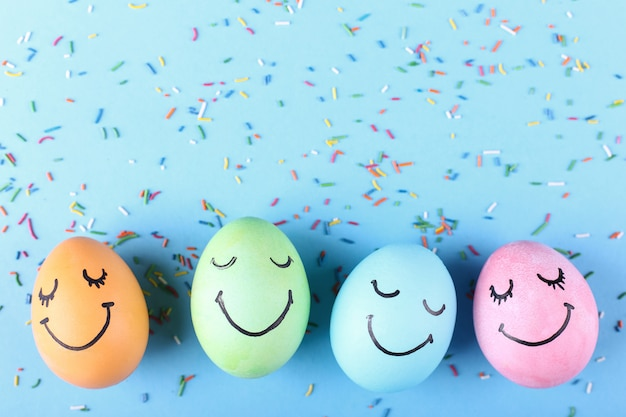Farbige eier mit gemaltem lächeln. fröhliche ostern konzept grußkarte design.