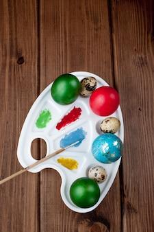 Farbige eier und farbe auf einem holztisch, osterhintergrund