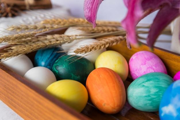 Farbige eier und weizenähren auf tablett