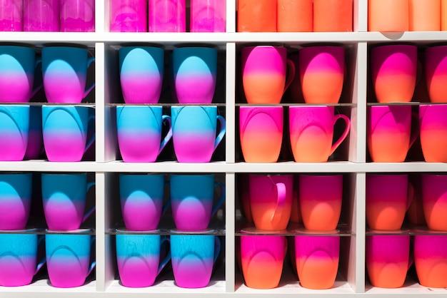 Farbige farbverlaufsgläser in den regalen im laden. tassen in allen farben des regenbogens auf der theke des ladens