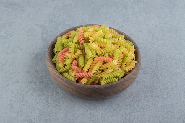 Farbige fusilli-nudeln in holzschale.