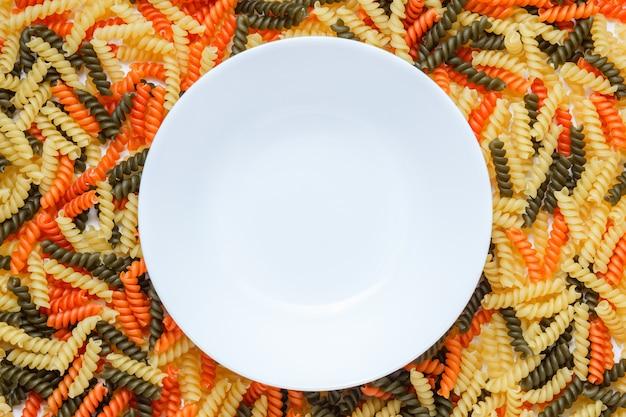 Farbige fusilli-nudeln mit weißer platte flach liegen