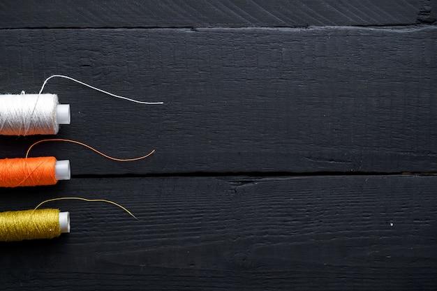 Farbige garnrollen zum nähen auf einem hölzernen schwarzen hintergrund. speicherplatz kopieren