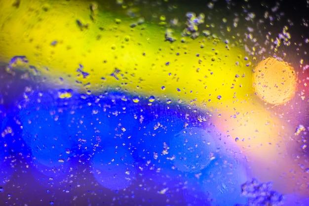 Farbige gelbe und blaue textur, verschwommene wassertropfen und helle flecken auf dem glas