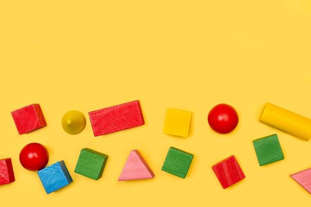 Farbige geometrische formstücke aus holz auf gelbem grund