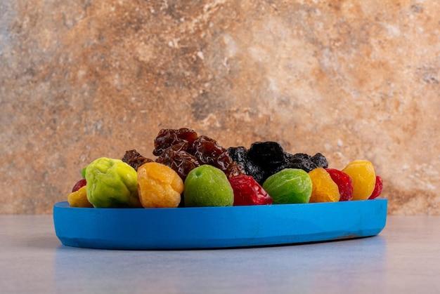 Farbige getrocknete kirschen und früchte auf betonoberfläche.