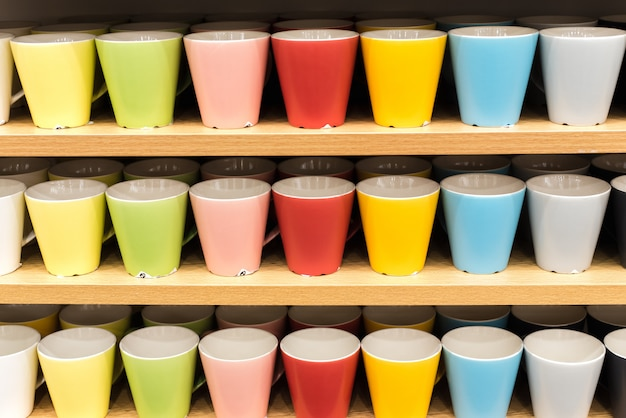 Farbige gläser in den regalen im laden. ups aller farben des regenbogens auf der theke des ladens
