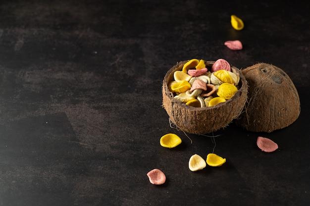 Farbige handgemachte nudeln in kokosnussplatte auf grauer weinlesewand, draufsicht
