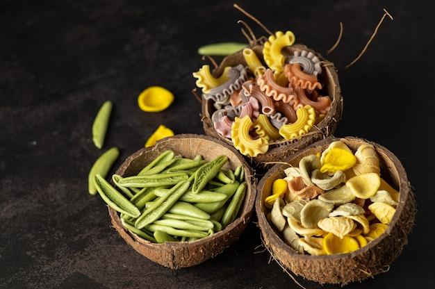 Farbige handgemachte nudeln mit natürlichen pflanzenfarben in kokosnuss-scarloop auf grauer vintage-wand, draufsicht