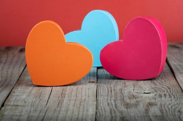Farbige herzförmige geschenkboxen auf holzsockel. valentinstag-konzept