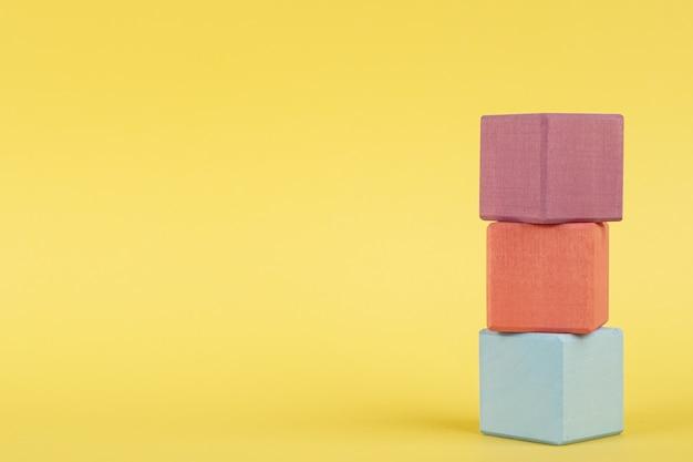 Farbige hölzerne würfel auf gelbem hintergrund, kinderbildung
