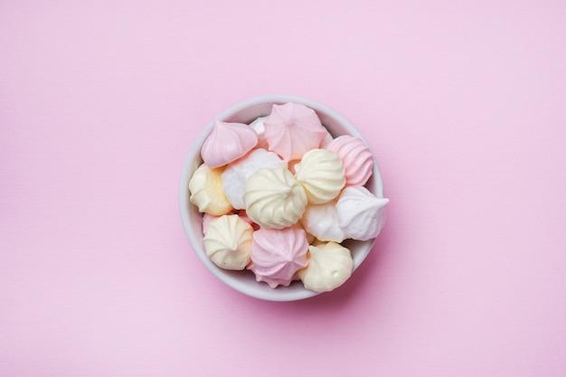 Farbige kleine baiser auf rosa. flachbaukonzept. kopieren sie platz.