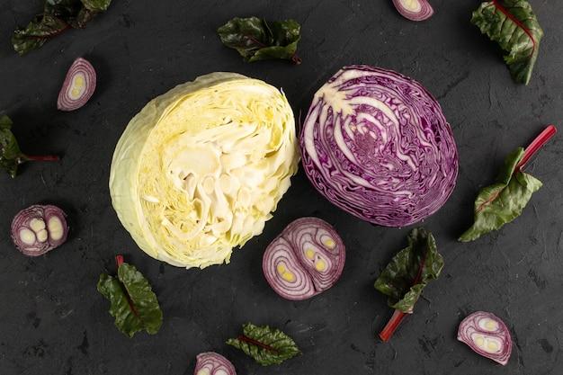 Farbige kohlfrüchte frisch reif und geschnittene gelbe und lila kohlköpfe und grüne blätter lokalisiert auf grauem hintergrund